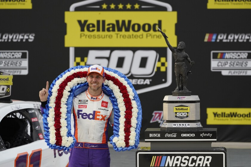 Denny Hamlin poses with the trophy after winning the NASCAR Cup Series auto race.