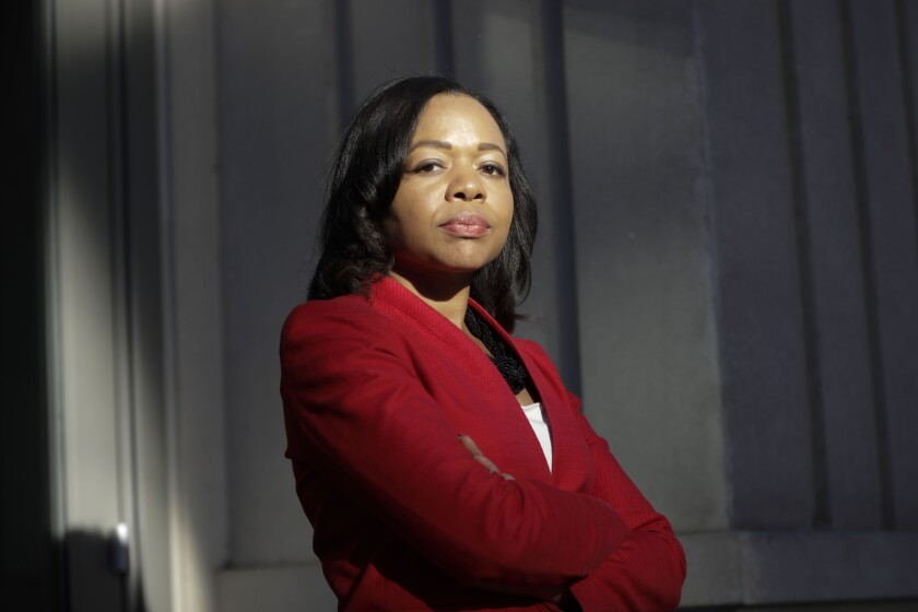 Kristen Clarke stands with arms crossed