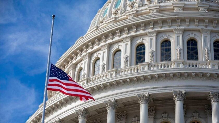 In honor of former President George H.W. Bush, the U.S. flag flies at half-staff outside the U.S. Capitol in Washington.