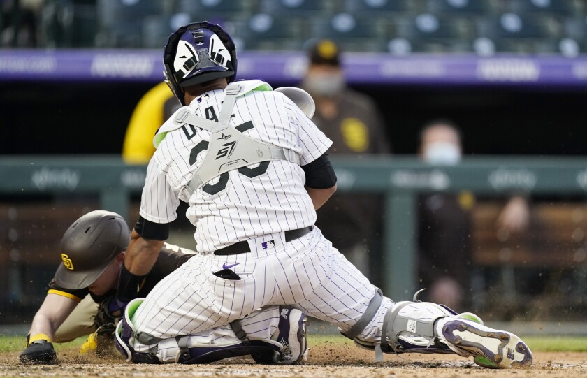 Rockies catcher Elias Diaz tags out the Padres' Jake Cronenworth
