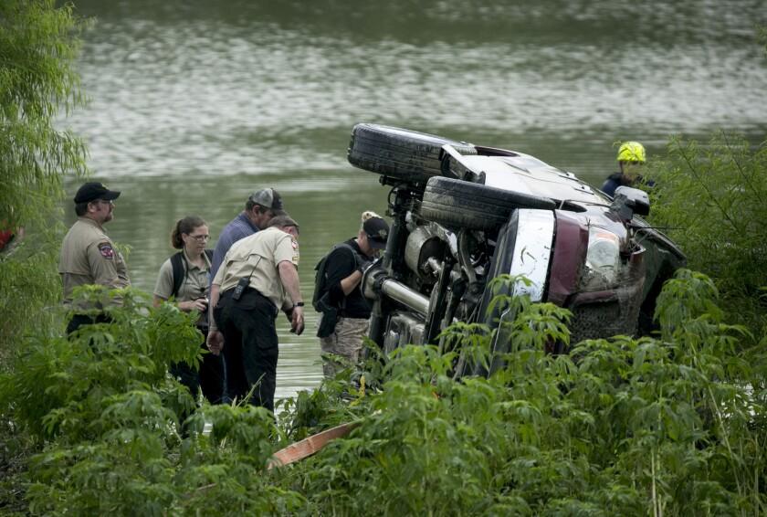 Un agente de la oficina del jefe de policía del condado Travis observa una camioneta que fue volcada por la corriente de una inundación y recuperada en el sur de Austin, Texas, el martes 31 de mayo de 2016. Rescatistas siguen buscando a una persona desaparecida. (Jay Janner/Austin American-Statesman vía AP)