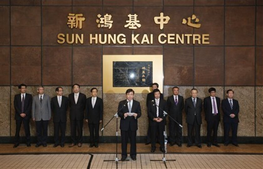 Sun Hung Kai Properties Joint Vice Chairmen and Managing Directors, Raymond Kwok Ping Luen, center, and Thomas Kwok Ping Kwong, fifth right, speak to the media as they stand next to their company management team outside the Sung Hung Kai headquarters building in Hong Kong Tuesday, April 3, 2012. Hong Kong's anti-corruption watchdog has arrested two senior executives at a listed company and a former senior government official for suspected corruption. (AP Photo/Kin Cheung)