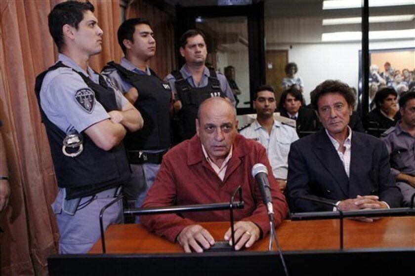 Former army intelligence operative Raul Guglielminetti, center, and former agent of Argentina's intelligence agency SIDE, Honorio Ruiz, sit in court before their sentencing in Buenos Aires, Argentina, Thursday March 31, 2011.  Guglielminetti was sentenced to 20 years in prison, while Ruiz was sente