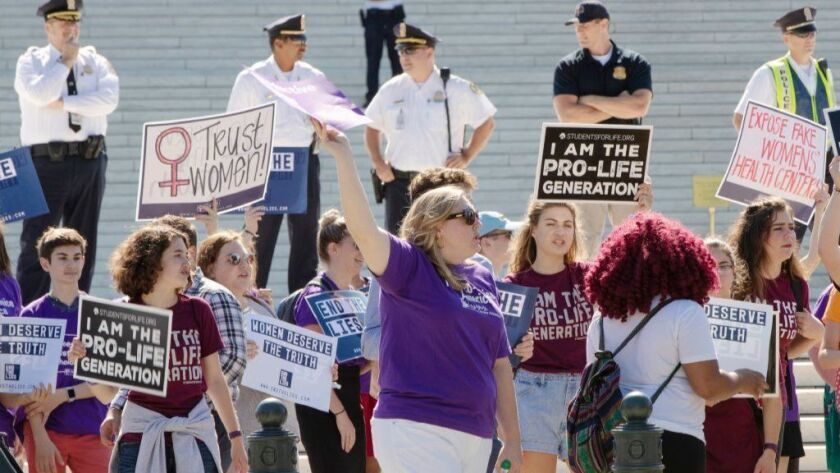 Abortion-rights and antiabortion advocates hold signs as they demonstrate in front of the Supreme Court in Washington on June 25, 2018.