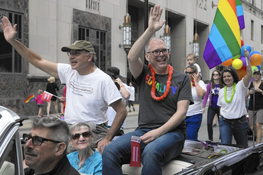 James Obergefell, right, a plaintiff in the Supreme Court case on same-sex marriage, takes part in a gay pride parade in Cincinnati on Saturday. The high court ruled 5 to 4 the day before that same-sex couples had the right to marry nationwide.