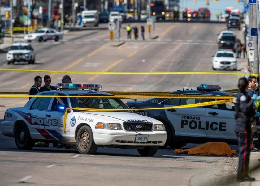 Vista de un cuerpo cubierto (d) después de que una camioneta alquilada recorriera la acera golpeando a los peatones en la calle Yonge en el norte de Toronto (Canadá). EFE/Archivo