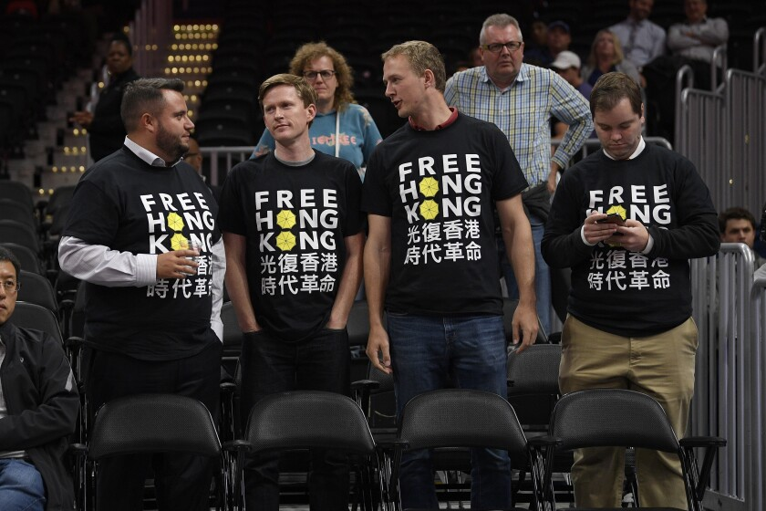 """Activists wear """"Free Hong Kong"""" T-shirts before an NBA exhibition basketball game between the Washington Wizards and the Guangzhou Loong-Lions, Wednesday, Oct. 9, 2019, in Washington. (AP Photo/Nick Wass)"""