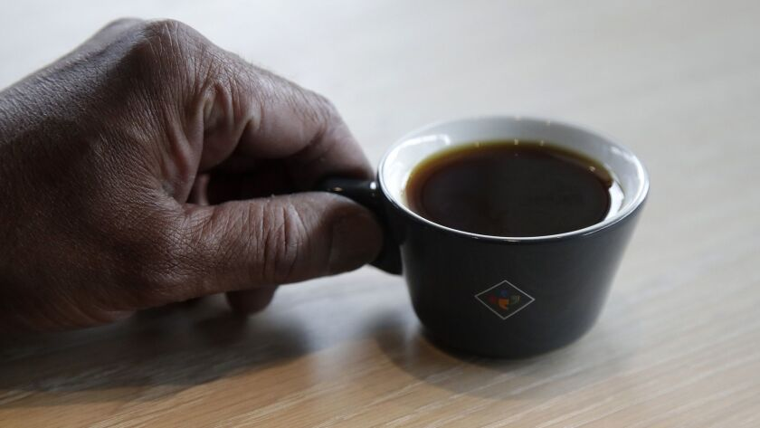 Klatch Coffee owner Bo Thiara holds a cup of Elida Natural Geisha coffee at his shop in San Francisc