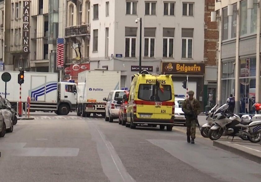 In this framegrab taken from APTN, a soldier walks along a street in Brussels, Belgium, Wednesday July 20, 2016. Police in Brussels say they arrested a man acting suspiciously and wearing heavy clothes with wires hanging out, in the area of place Monnaie. Police closed the area and evacuated people