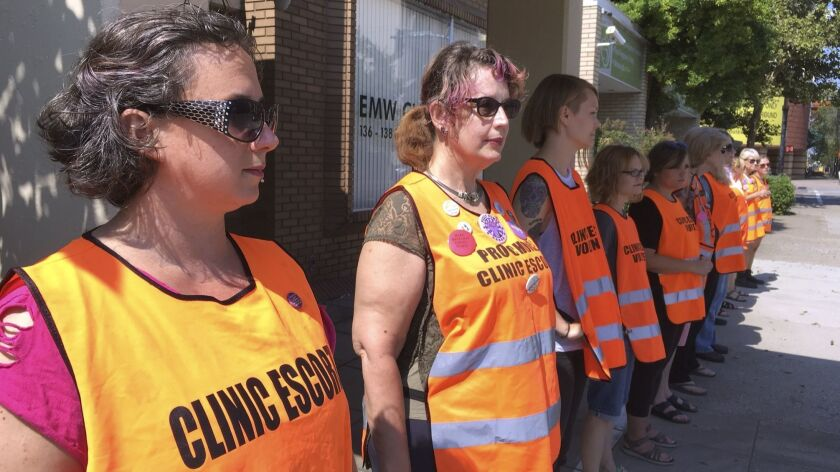 Escort volunteers line up outside the EMW Women's Surgical Center in Louisville, Ky., in July 2017.