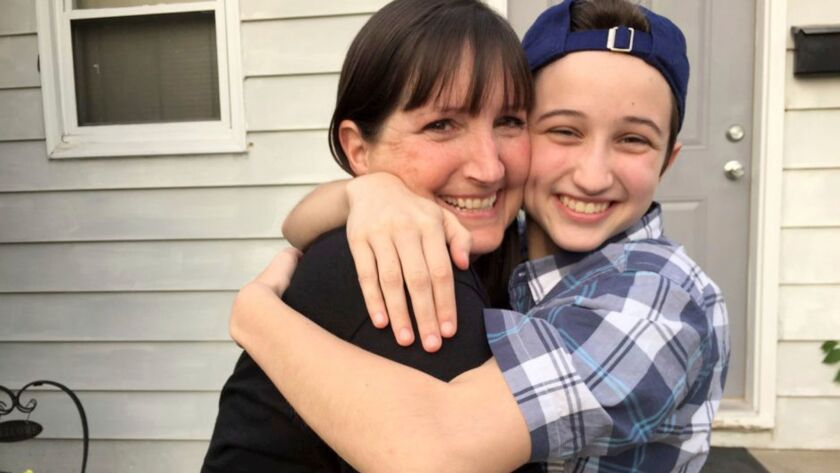 In this undated photo provided by the Transgender Law Center, Ashton Whitaker hugs his mother, Melissa, in Kenosha, Wis.