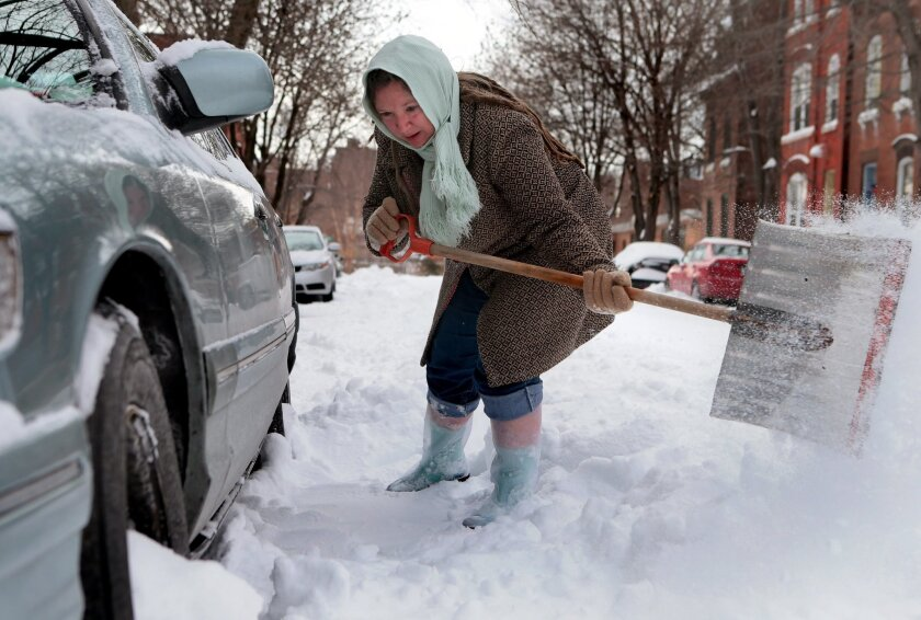 Gilda Mosely digs her car out from the snow outside her home on Tuesday, Jan. 7, 2014, in Soulard, Mo. Tuesday was the worst cold snap in nearly two decades for Missouri. (AP Photo/St. Louis Post-Dispatch, Laurie Skrivan) EDWARDSVILLE INTELLIGENCER OUT; THE ALTON TELEGRAPH OUT