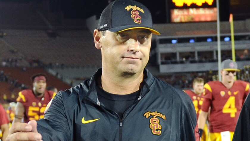 USC head coach Steve Sarkisian, left, walks off the field after the Trojans' loss to Washington in October.
