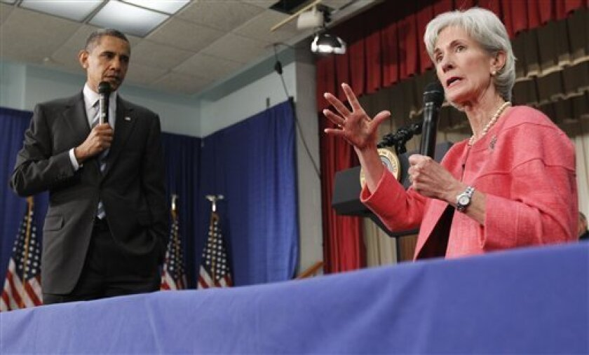 FILE - In this June 8, 2010 file photo, President Barack Obama listens as Health and Human Services Secretary Kathleen Sebelius speaks during a town hall meeting on the Affordable Care Act, at the Holiday Park Multipurpose Senior Center in Wheaton, Md. Medicare's prescription coverage gap is gettin
