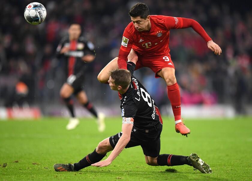 Bayern Munich's Robert Lewandowski challenges Bayer Leverkusen's Lars Bender during a Nov. 30 game at Allianz Arena.