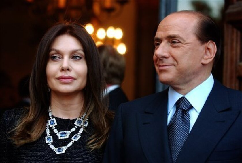 FILE - In this Friday June 24, 2004 file photo, Italian premier Silvio Berlusconi, right, and his wife Veronica Lario wait for President George W. Bush and first lady Laura Bush at the Villa Madama residence for a social dinner, in Rome. On Sunday, May 3, 2009 two Italian newspapers reported that Premier Silvio Berlusconi's wife is seeking a divorce. La Stampa and La Repubblica dailies say Veronica Lario had retained a divorce attorney to begin the process of legal separation and divorce. Berlusconi's office said it had no comment Sunday. (AP Photo/Susan Walsh, File)