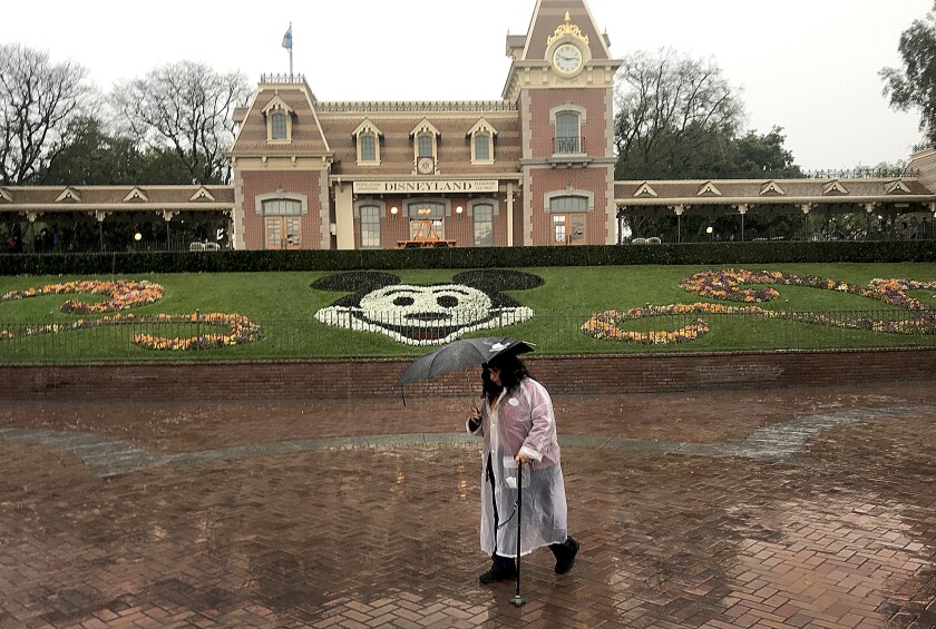 A Disneyland employee walks through the entrance to Disneyland during a rain shower in Anaheim on Thursday.