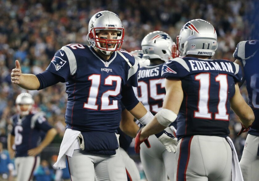 New England Patriots quarterback Tom Brady (12) celebrates his touchdown pass to wide receiver Julian Edelman (11) in the second half of an NFL football game against the Miami Dolphins, Thursday, Oct. 29, 2015, in Foxborough, Mass. (AP Photo/Michael Dwyer)