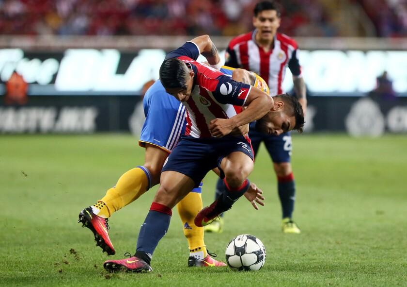 El delantero Alan Pulido es frenado en un avance de las Chivas.