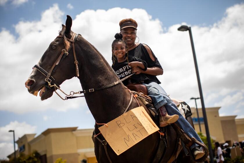 Taylor Rahye Wade, 3, daughter of Keiara Wade, an official Compton Cowboy, rides with her grandmother, Jennifer McClendon.