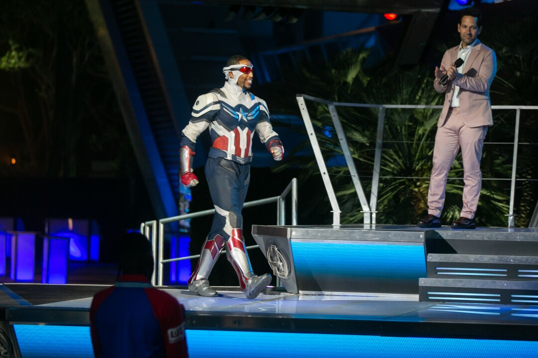 An actor dressed as Captain America takes the stage as Paul Rudd applauds.