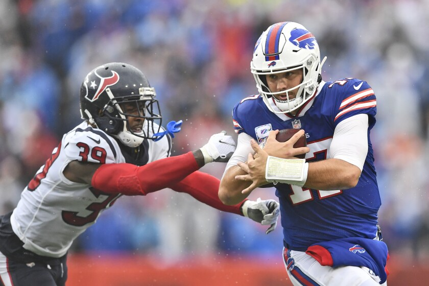 Buffalo Bills quarterback Josh Allen, right, runs past Houston Texans cornerback Terrance Mitchell during the first half of an NFL football game, Sunday, Oct. 3, 2021, in Orchard Park, N.Y. (AP Photo/Adrian Kraus)