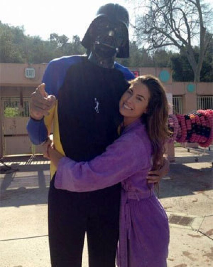 "Basketball legend Kareem Abdul-Jabbar, left, poses with model Katherine Webb on the set of the reality TV show ""Splash."""