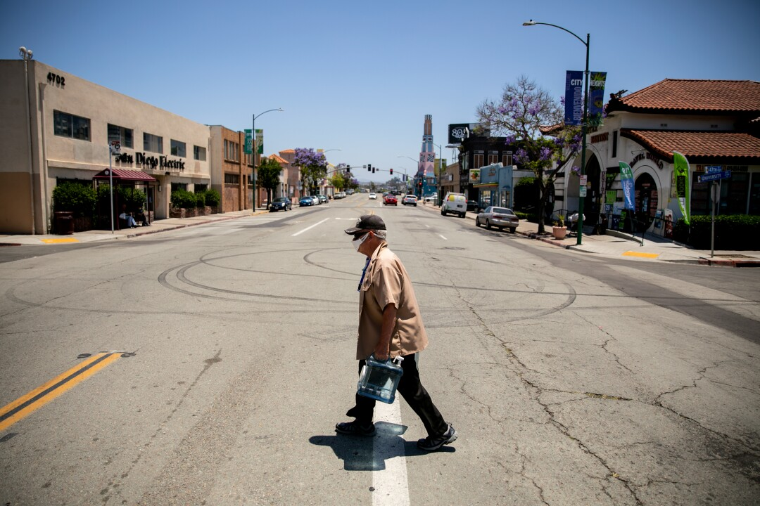 Ron Dobbins, 75, who lives about a block away from the number 7 bus stop, carries water back to his home.