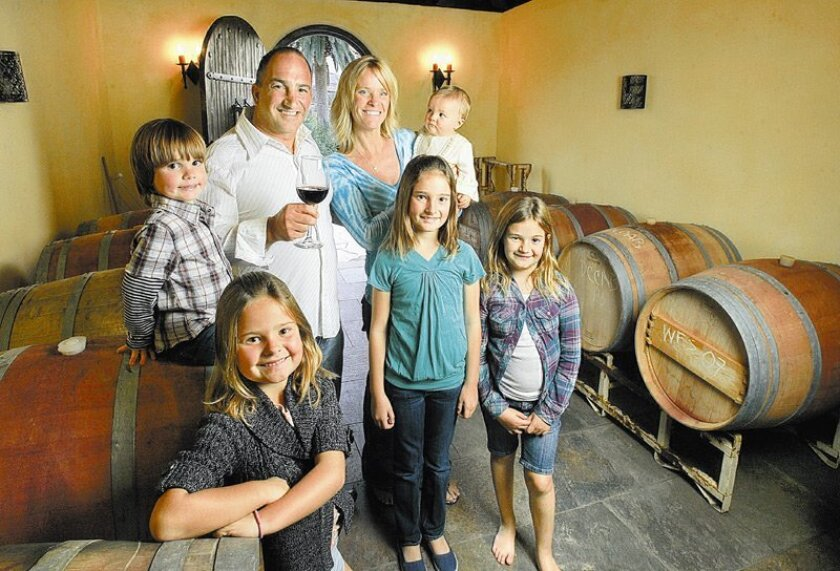 Mike Battiata, Realtor, winemaker and former tall ships captain, at home with his wife, Amy, in their wine cave with their five children: (from left) Sal, 3; Maddie, 7; Sophia, 10; 8-month-old Elle; and Mia, 8. As a hobby, Battiata makes wine the way his father did.