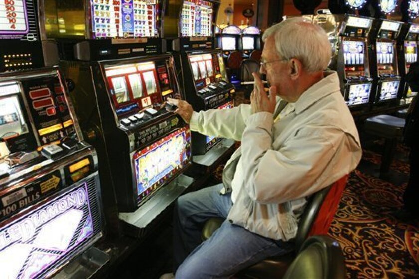 This April 8, 2008 file photo shows Bob Phelan of Pawleys Island, S.C. smoking as he plays a slot machine at the Trump Taj Mahal in Atlantic City, N.J.. New Jersey put off a smoking ban for Atlantic City casinos after five of 11 casinos there warned they could file bankruptcy by year's end. (AP Photo/Cie Stroud,File)