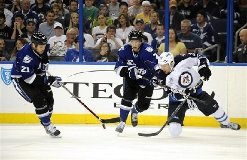 Tampa Bay Lightning right wing Brandon Segal, left, and defenseman Keith Aulie, center, battle for the puck against Winnipeg Jets right wing Blake Wheeler during the first period of an NHL hockey game on Saturday, March 31, 2012, in Tampa, Fla. (AP Photo/Brian Blanco)