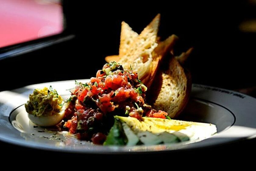 Ahi tuna tartare is served with a stack of thin toasts and a fan of avocado.
