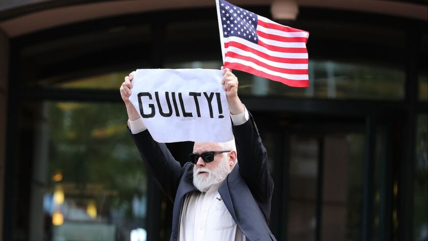 A demonstrator holds up a sign and flag after leaving the courthouse following the verdict announcement Tuesday in the trial of former Trump campaign manager Paul Manafort in Alexandria, Va.