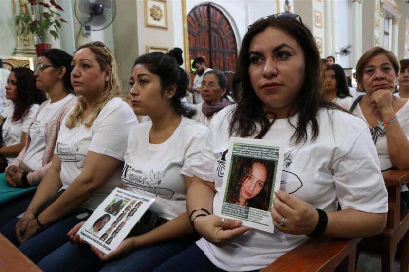 Una mujer sostiene una foto de su familiar desaparecida durante una misa en la catedral del Señor Santiago este domingo en Chilpancingo (México). EFE/Archivo