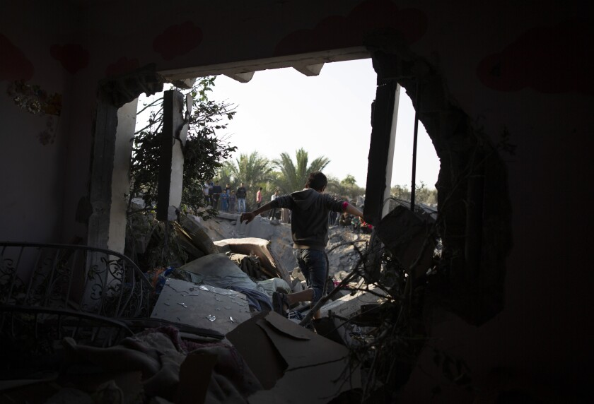 A Palestinian boy walks walks through a home in the Gaza Strip that was destroyed during Israeli airstrikes.