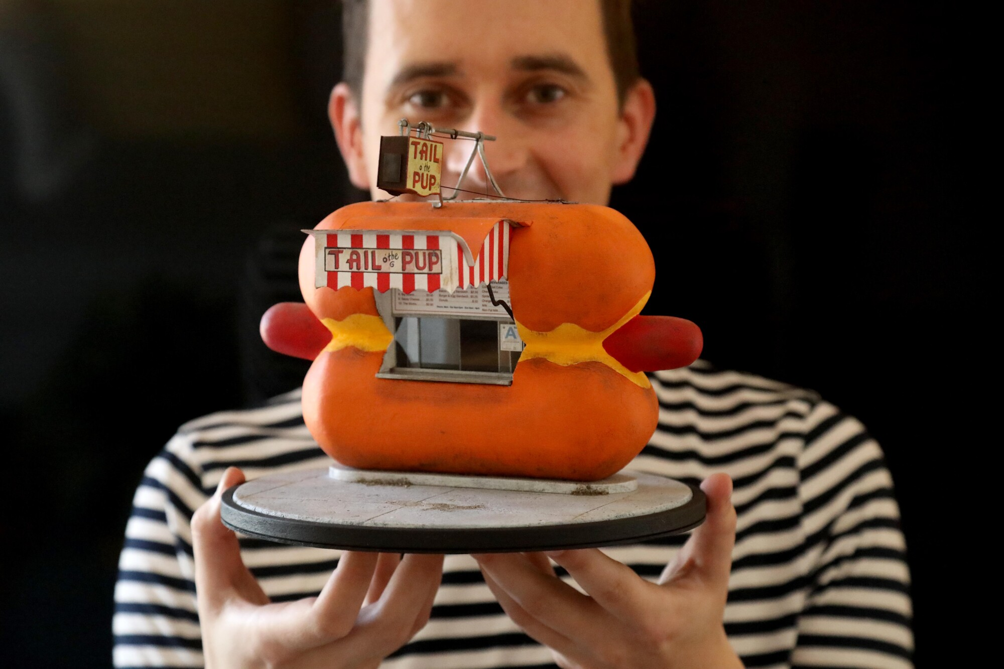 Kieran Wright holds his miniature model of a hotdog-shaped hotdog stand