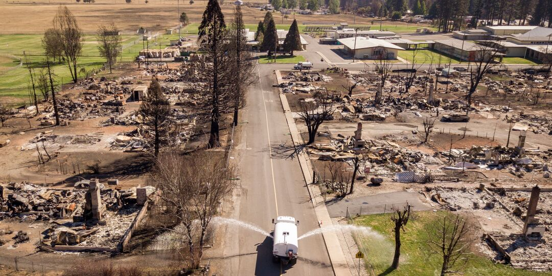 An aerial picture taken on September 24, 2021 a water truck sprays down the burned remains