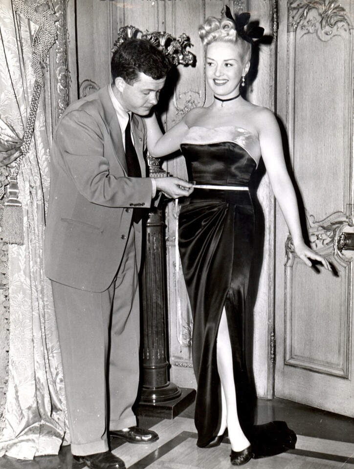 Associated Press reporter Bob Thomas playfully measures the waistline of pinup queen Betty Grable upon her return to work after childbirth. She enjoyed the stunt, he said.