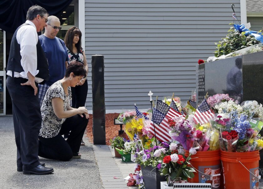 Mourners, including Jennifer Bohn, kneeling, her husband Randy Bohn, center, and Scott Veau, left, pause before a memorial set up for slain police Officer Ronald Tarentino outside the police station, Monday, May 23, 2016, in Auburn, Mass. Tarentino was fatally shot during a traffic stop in Auburn o