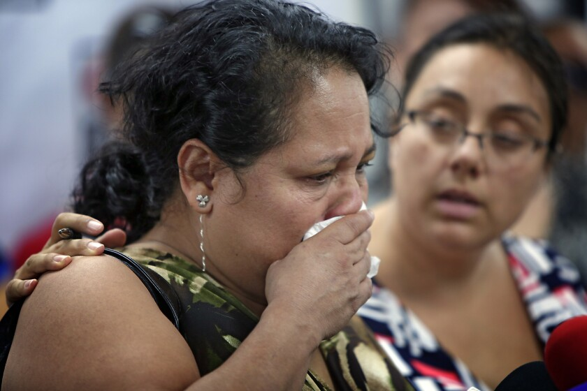 Gloria Torres becomes emotional during a news conference Thursday, where she and other former employees of Vynl Technology Inc. said they had been pressured to resign amid an audit by U.S. Immigration and Customs Enforcement.
