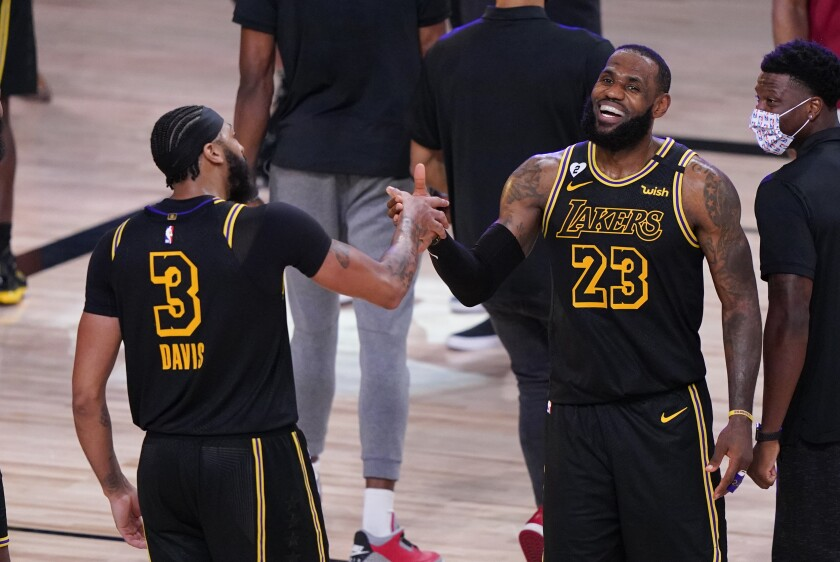 Anthony Davis and LeBron James celebrate after the Lakers beat Denver in Game 2 of their playoff series on Sunday.