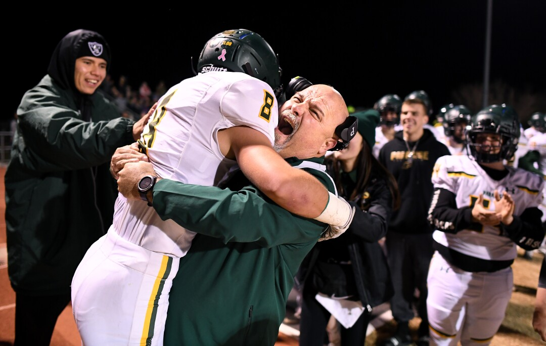 Brenden Moon is hugged on the sideline by assistant coach Nino Pinocchio after his touchdown.