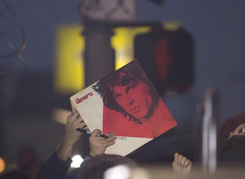 """Un fanáticos de la banda de rock estadounidense The Doors muestra una copia del álbum debut de la banda hoy, miércoles 4 de enero de 2017, durante un homenaje en Venice Beach, California (EE.UU). La ciudad de Los Ángeles declaró hoy el """"Day of The Doors"""" (Día de The Doors), coincidiendo con el 50 aniversario de su disco debut el 4 de enero de 1967, en un acto oficial al que asistieron los miembros de la legendaria banda John Densmore y Robby Krieger. EFE"""