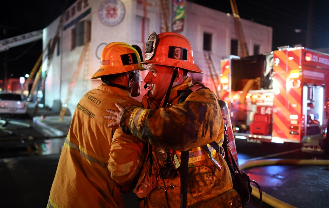 Station No. 9 firefighter Ray Robles, right, hugs a comrade after battling a predawn fire in downtown Los Angeles