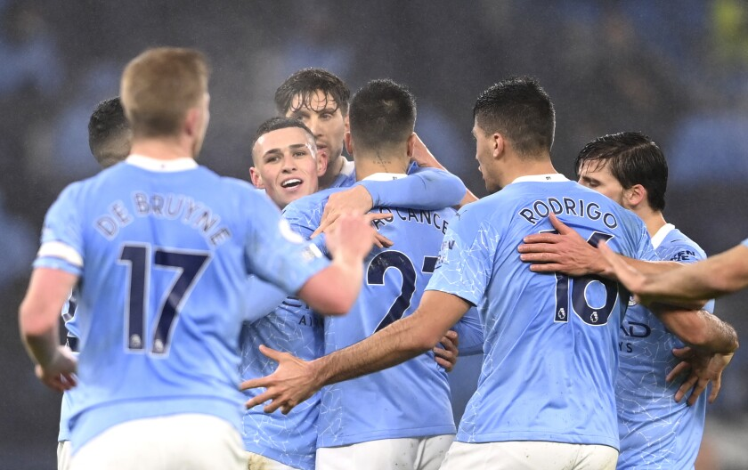 Manchester City's Phil Foden, centre, celebrates after scoring his side's opening goal during the English Premier League soccer match between Manchester City and Brighton and Hove Albion at the Etihad Stadium in Manchester, England, Wednesday, Jan. 13, 2021. (Laurence Griffiths, Pool via AP)