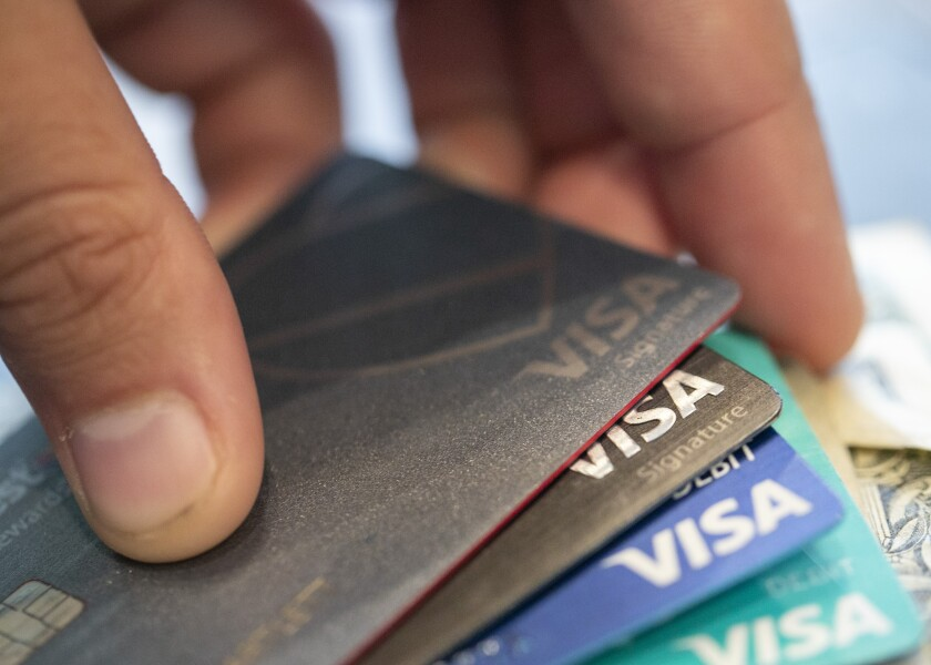 FILE - This Aug. 11, 2019 file photo shows Visa credit cards in New Orleans. U.S. consumers increased their borrowing in December 2020 by $9.7 billion, as Americans took out loans to buy autos or finance their educations. But credit card use declined for the third-consecutive month. (AP Photo/Jenny Kane, File)