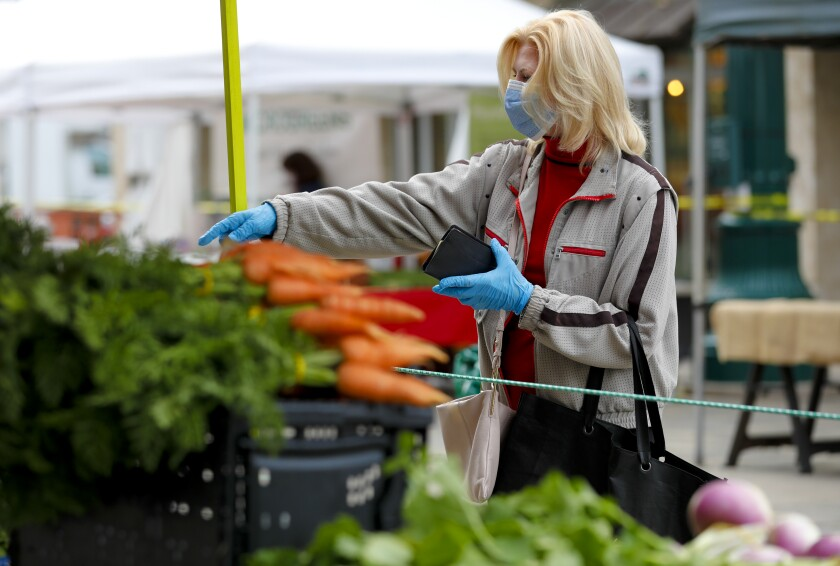 Gail Donahue pointed to the fresh vegetables she wanted at the Farmer Market in Little Italy.