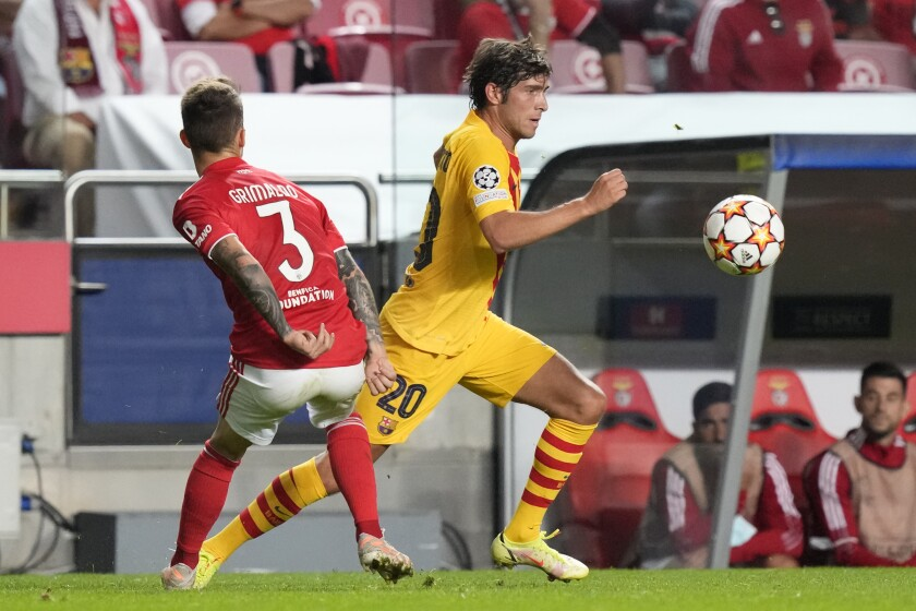 Barcelona's Sergi Roberto, right, gets past Benfica's Alex Grimaldo during a Group E Champions League soccer match between Benfica and Barcelona at the Luz stadium in Lisbon, Portugal, Wednesday, Sept. 29, 2021. (AP Photo/Armando Franca)