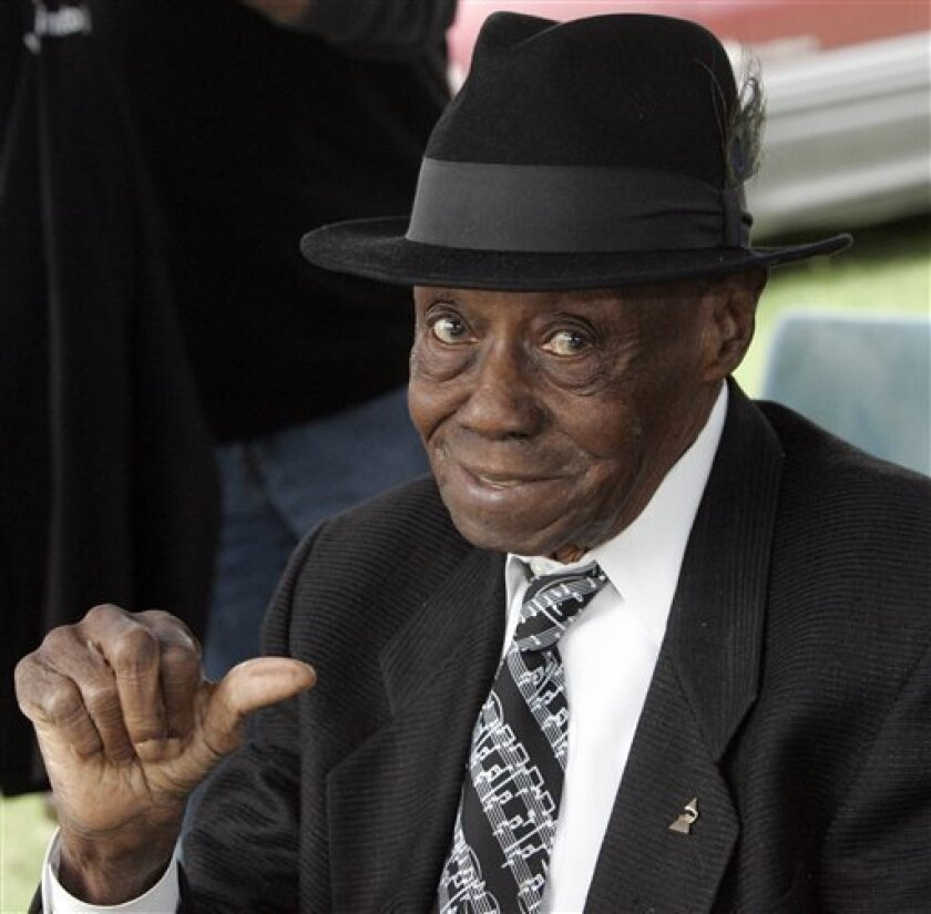 """FILE - In this Oct. 11, 2009 file photo, Grammy winning blues pianist Joe Willie """"Pinetop"""" Perkins motions a """"thumbs up"""" gesture during the annual festival at Hopson Plantation in Clarksdale, Miss. Perkins, one of the last old-school bluesmen and oldest Grammy winner, died at his home of cardiac arrest Monday, March 21, 2011, his manager said. He was 97. (AP Photo/Rogelio V. Solis, File)"""