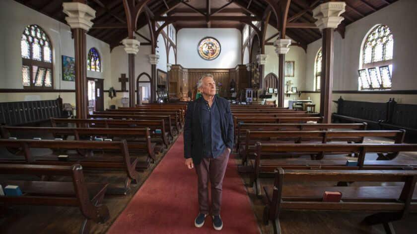 Father Tom Carey stands inside The Church of the Epiphany in Lincoln Heights, which was built in 1913.